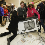 """Shoppers wrestle over a television as they compete to purchase retail items on """"Black Friday"""" at an Asda superstore in Wembley, north London November 28, 2014. Britain's high streets, malls and online sites were awash with discounts on Friday as more retailers than ever embraced U.S.-style """"Black Friday"""" promotions, seeking to kickstart trading in the key Christmas period. In the United States the Friday following the Thanksgiving Day holiday is called Black Friday because spending usually surges and indicates the point at which American retailers begin to turn a profit for the year, or go """"into the black"""". REUTERS/Luke MacGregor  (BRITAIN - Tags: BUSINESS ANNIVERSARY TPX IMAGES OF THE DAY)"""